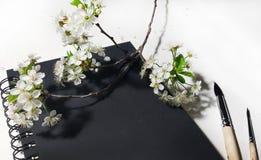 开花与黑笔记本和刷子的樱桃 库存图片
