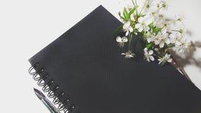 开花与黑笔记本和刷子的樱桃 免版税图库摄影