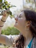 开花嗅到少年结构树的女孩桔子 免版税图库摄影