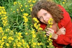 开花嗅到的妇女黄色年轻人 免版税库存照片