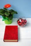 开花在一个罐和一本红色书和一个玻璃花瓶有玫瑰花瓣的 免版税库存照片