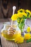 开花在一个玻璃瓶子和蒲公英的蜂蜜 库存图片