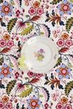 开花在与一只黄色蝴蝶的一种用花装饰的织品掩藏的板材 免版税图库摄影