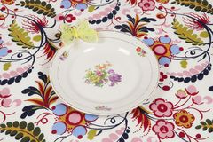 开花在与一只黄色蝴蝶的一种用花装饰的织品掩藏的板材 免版税库存照片