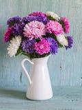 开花在白色上釉的投手的翠菊 免版税库存照片
