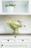 开花在白色梳妆台的装饰 轻的花卉家庭装饰 免版税库存照片