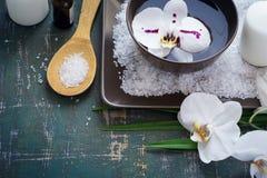 开花在碗的白色兰花水和温泉设置 免版税库存照片