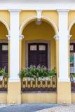 开花在阳台在黄色古色古香的样式大厦 免版税库存图片