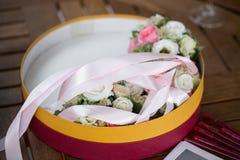 开花构成,婚姻桃红色玫瑰镯子与丝带和新郎钮扣眼上插的花的在木桌上 库存照片
