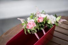 开花构成,婚姻桃红色玫瑰镯子与丝带和新郎钮扣眼上插的花的在木桌上 库存图片