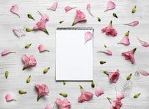 开花构成 有桃红色花和叶子的笔记本 顶视图,平的位置 免版税库存图片