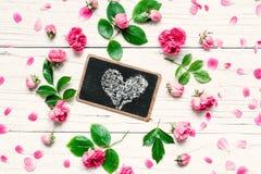 开花构成 框架由与心脏的新鲜的玫瑰色花制成在黑板在白色木背景 免版税库存图片