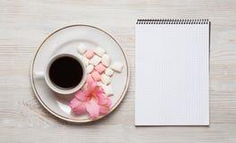 开花构成 笔记本和咖啡与桃红色花和叶子的 顶视图,平的位置,文本的地方 库存照片