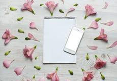 开花构成 笔记本和电话有桃红色花和叶子的 顶视图,平的位置 图库摄影