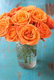 开花桔子玫瑰色花瓶 免版税库存照片