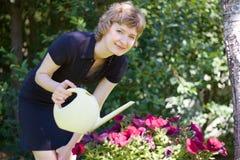 开花浇灌的妇女 图库摄影