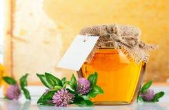 开花甜玻璃蜂蜜的瓶子 免版税图库摄影