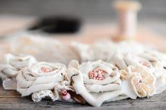 开花由棉织物做的项链,鞋带整理,小珠和毛毡基地在木背景 夏天纺织品首饰 免版税库存图片