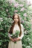开花的丁香的美丽的女孩 库存图片