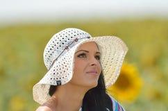 开花的向日葵领域的年轻俏丽的妇女在夏天 免版税库存图片