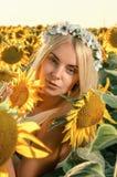 开花的向日葵领域的年轻美丽的妇女 免版税库存照片