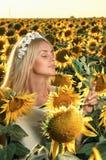 开花的向日葵领域的年轻美丽的妇女 免版税库存图片