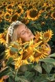 开花的向日葵领域的年轻美丽的妇女 库存图片