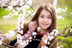 开花的庭院的愉快的女孩在春天 免版税库存图片