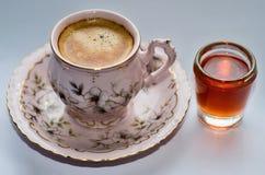 开花的微小的咖啡和玻璃用红色果子利口酒 免版税库存照片