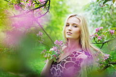 开花的春天树的年轻可爱的妇女 免版税库存照片