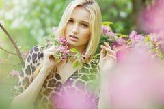 开花的春天树的年轻可爱的妇女 免版税图库摄影