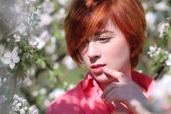 开花的树背景的,在开花的树的春天时尚女孩室外画象,秀丽浪漫妇女红发女孩 免版税库存照片