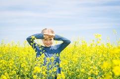 开花的油菜籽领域的愉快的女孩在夏天 免版税库存照片