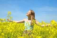 开花的油菜籽领域的年轻愉快的妇女 图库摄影