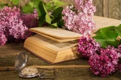 开花的淡紫色分支、书和时钟的构成 免版税库存图片