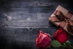 开花的玫瑰花蕾包裹了在木的当前箱子 免版税库存图片