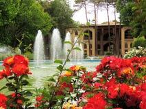 开花的红色伊斯法罕Hasht Behesht宫殿由喷泉开花 免版税库存照片