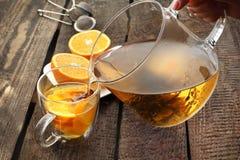 开花的绿茶用桔子,一杯热的芳香饮料 免版税图库摄影