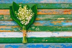 开花芬芳百合花束在色的木减速火箭的难看的东西背景的 免版税库存照片