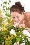 开花花从事园艺嗅到的妇女 图库摄影