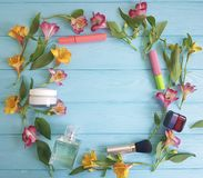 开花装饰德国锥脚形酒杯蓝色木背景样式化妆用品的框架 库存照片