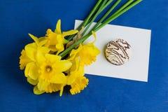 水仙开花,信封,在蓝色背景的蛋白软糖 图库摄影