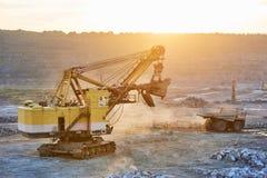 开采 挖掘机和翻斗车在露天开采的花岗岩或的铁 库存图片