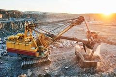 开采 挖掘机装货花岗岩或矿石到翻斗车里 图库摄影