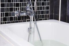 开阔水域从龙头到浴缸在卫生间里 库存照片