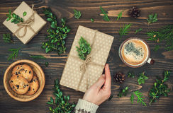 开头圣诞节礼物 Woman& x27; s递拿着在土气木桌上的装饰的礼物盒 顶上,平的位置,顶视图 免版税库存图片