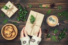 开头圣诞节礼物 Woman& x27; s递拿着在土气木桌上的装饰的礼物盒 顶上,平的位置,顶视图 免版税图库摄影