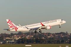 离开从悉尼机场的维尔京澳大利亚巴西航空工业公司地方喷气机ERJ-190 免版税库存图片