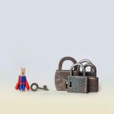 开头概念照片 锁着的挂锁 超级英雄在蓝色,红色衣服的开启者字符与钥匙和金属在梯度锁 免版税库存照片