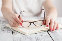 离开玻璃的惊奇的女实业家,当读在办公室时 库存图片